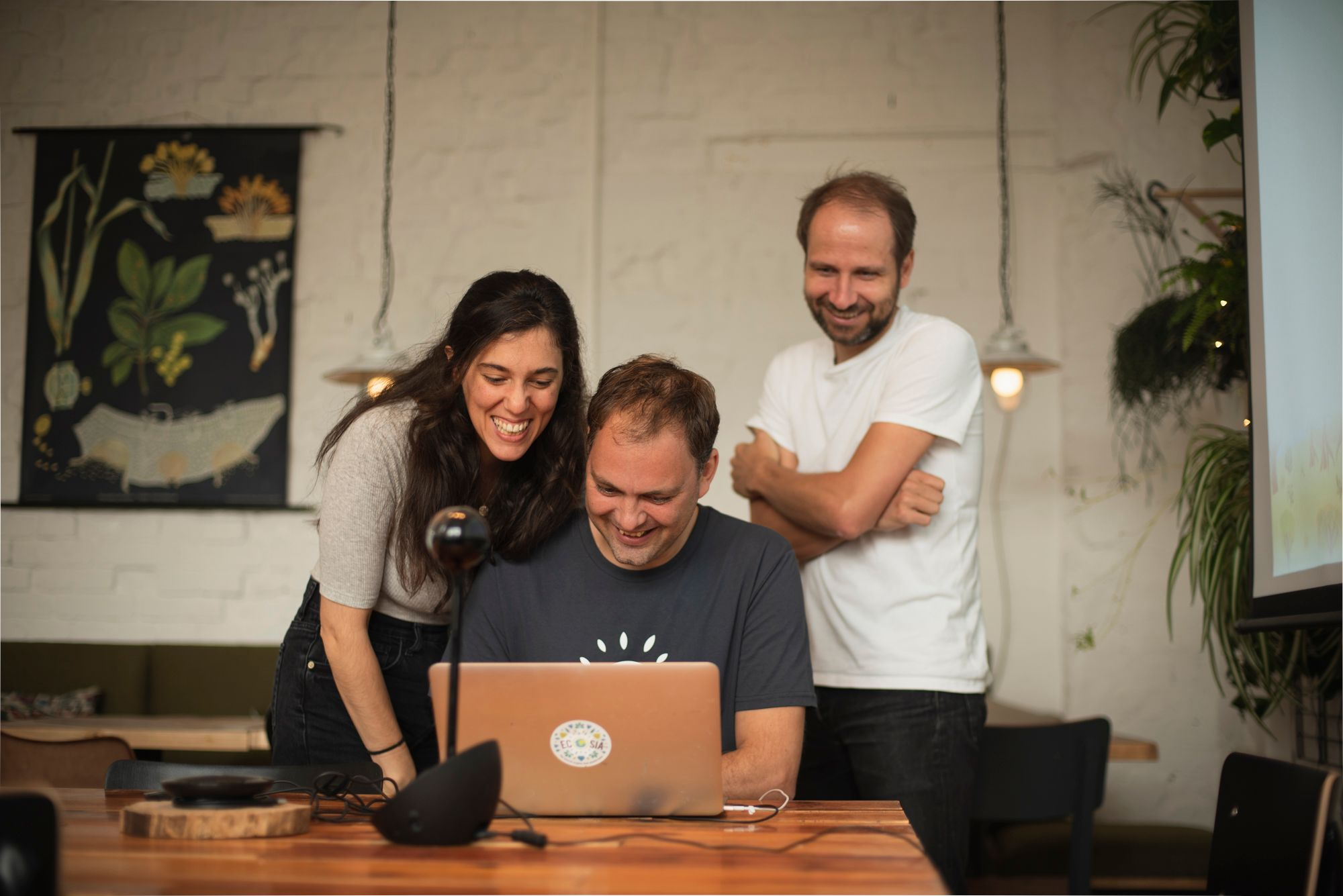 Three team members look onto a laptop, smiling.