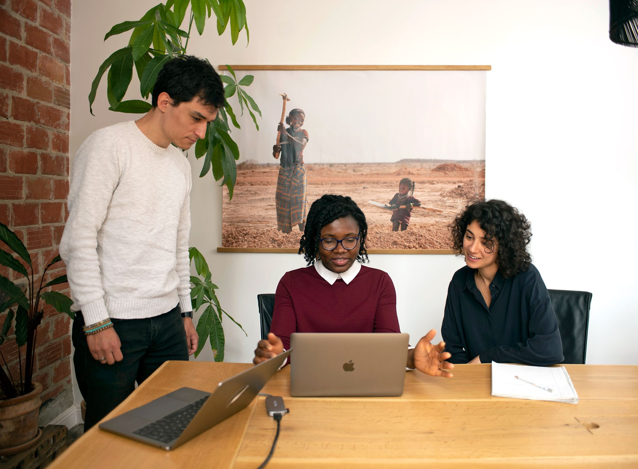 3 diverse colleagues discuss at a laptop