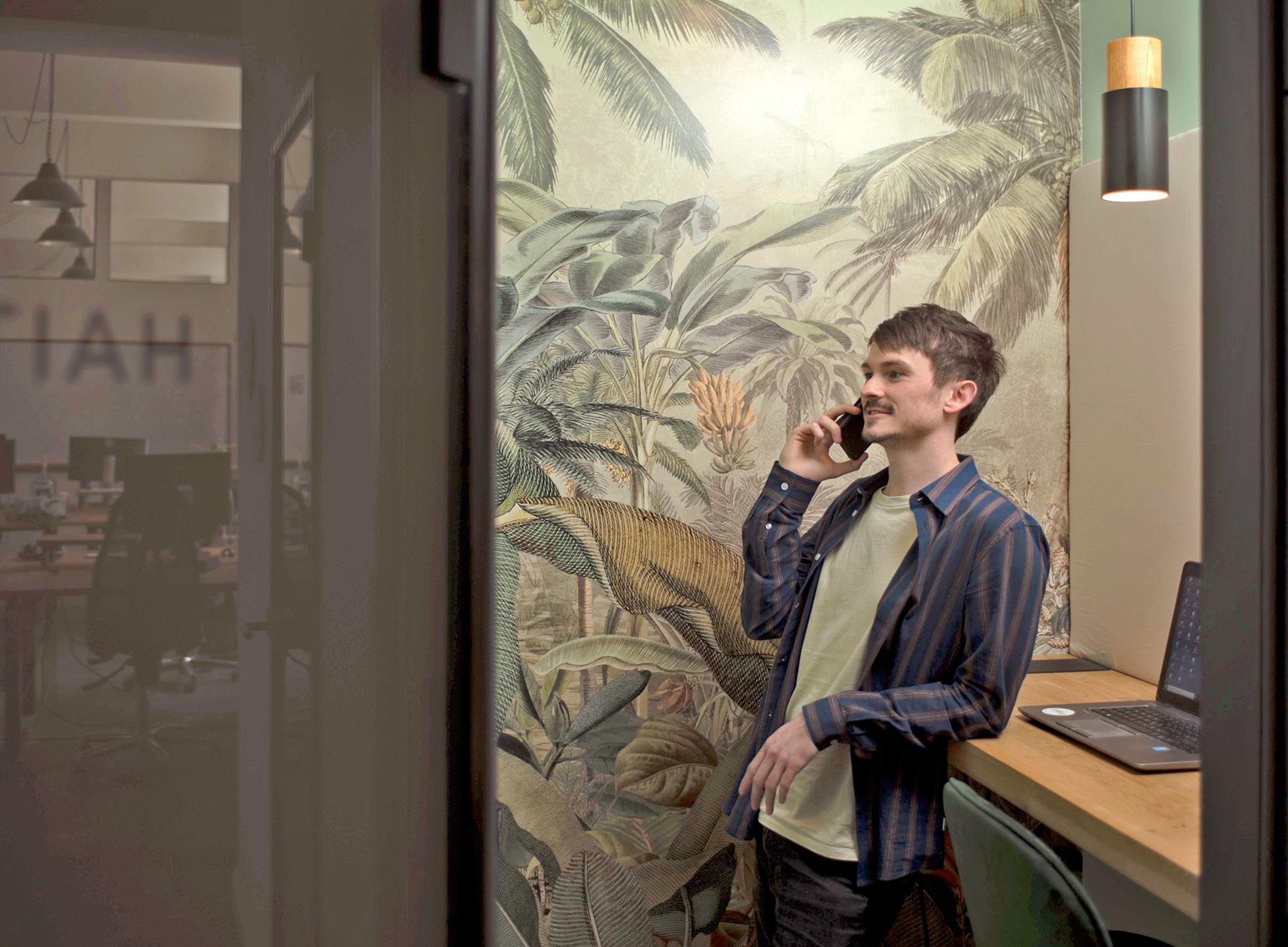 A colleague makes a call in a beautifully designed telephone booth