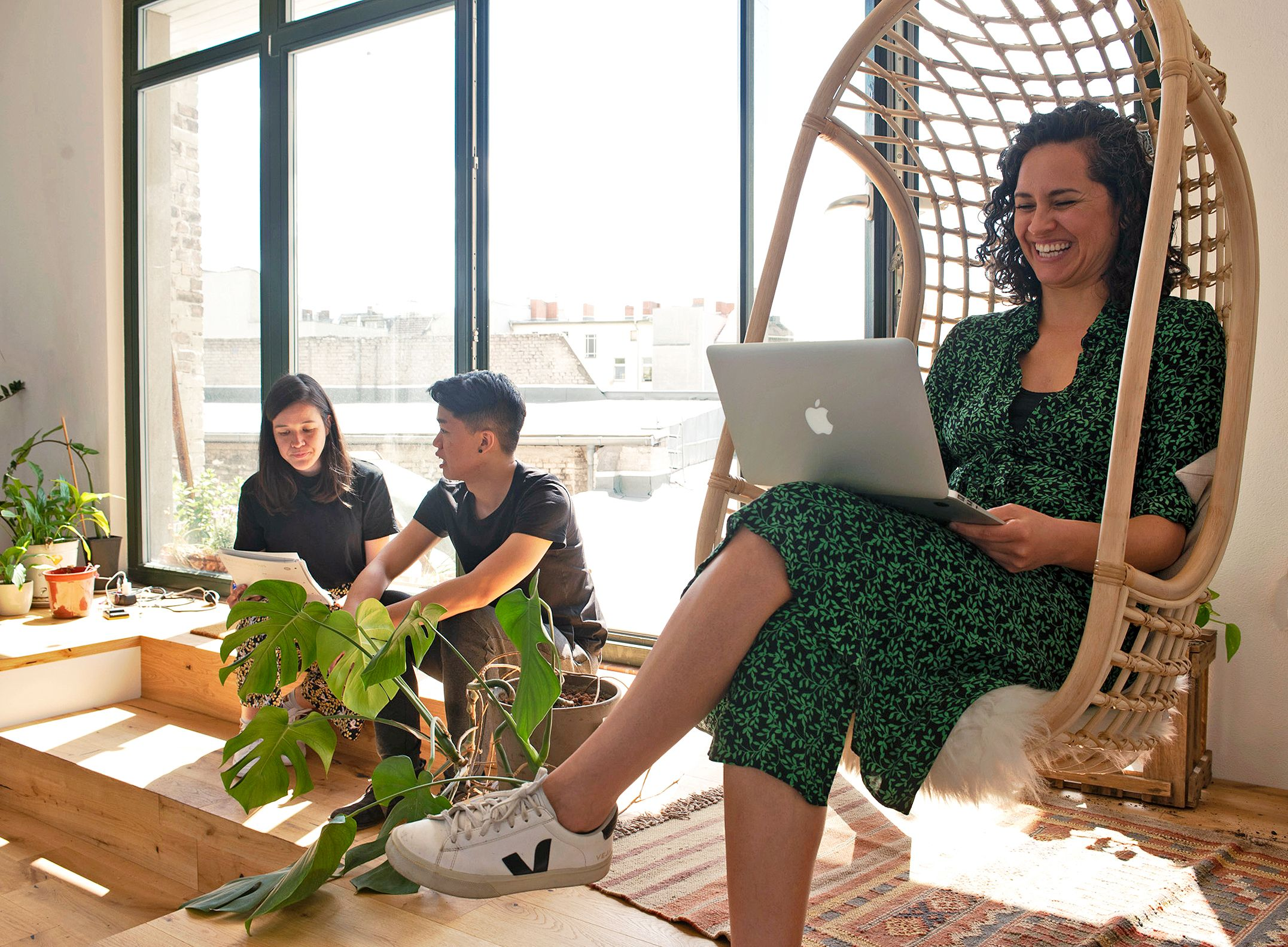 A smiling colleague works on her laptop in the sun, in a swing chair